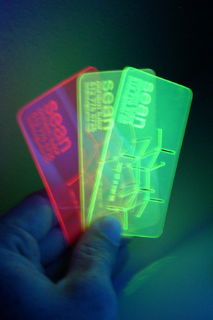 Business card in three colors of material, under UV light to show fluorescence.