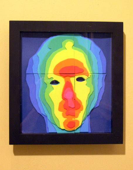A dimensional face formed by raised topographic layers in colors proceeding through the spectrum from blue (deepest) to hot pink (highest), set in a square black frame.